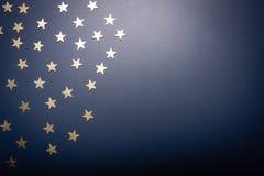 Guld- stjärnor isolerade blå bakgrund för omn med kopieringsutrymme arkivbild