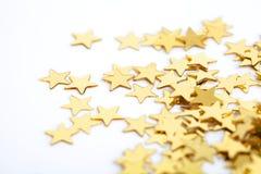 Guld- stjärnor som en bakgrund för jul Arkivbild