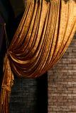 Guld- stor gardin på tegelstenväggen arkivbilder