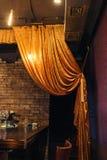 Guld- stor gardin på tegelstenväggen royaltyfri fotografi