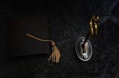 Guld- tangent och akademikert lock royaltyfri foto