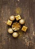 Guld- tappningbollar och gåvor med blänker på träbakgrund Arkivbild