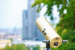 Guld- teleskop som riktas in mot staden arkivbild