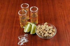 Guld- tequila med citronen, pistachos, cacahuate, och att salta Drinkar starksprit arkivfoto