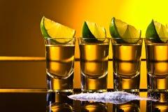Guld- tequila med limefrukt royaltyfri bild