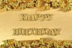 Guld- text för lycklig födelsedag och guld- gåvor på ett guld- Royaltyfri Foto