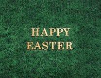 Guld- text för lycklig påsk som lägger i grönt gräs arkivbilder