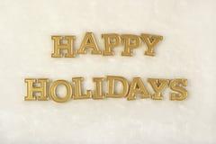 Guld- text för lyckliga ferier på en vit Arkivfoton
