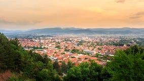 Guld- timmehimmel över den solbelysta Pirot staden royaltyfri foto