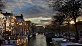 Guld- timmesolnedgång på kanalerna i Amsterdam royaltyfri fotografi