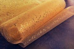 Guld- tråd och gliters på tygtexturen Textilrulle med vågor och skrynklor på den mörka kosmiska stenen ytbehandlar Begrepp Desi royaltyfri foto