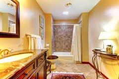 Guld- trevligt badrum med bruna keramiska tegelplattor Royaltyfri Foto