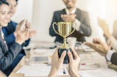 Guld- trofé för vinnande affärslag, lyckligt samtycke för affärslag royaltyfria bilder