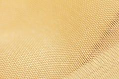 Guld- tyg som en bakgrund Makro Royaltyfri Foto