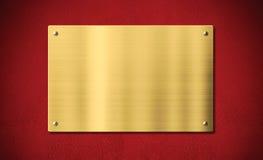Guld- utmärkelseplatta eller platta på röd bakgrund Arkivfoto