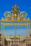 Guld- utsmyckade portar av slotten av Versailles över blå himmel P Royaltyfri Bild