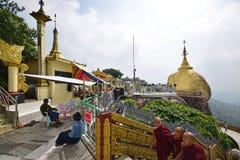 Guld- vagga på rätt & tempelbyggnad på vänstert med små buddistiska munkar som kommer från rätten på den Kyaiktiyo pagoden Royaltyfri Fotografi