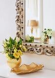 Guld- vas med blommor nära den härliga antika spegeln Fotografering för Bildbyråer