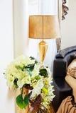 Guld- vas med blommor nära den härliga tabelllampan Arkivfoto