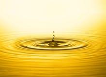 guld- vatten för droppe arkivbild