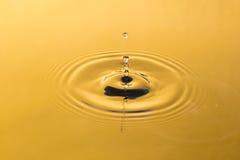 Guld- vatten och vattendroppe Arkivbilder
