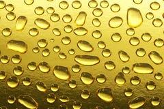 Guld- vattendroppar Arkivfoto