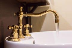 Guld- vattenkran- och handfatdesign Arkivbilder
