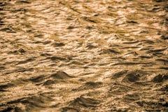 Guld- vattenyttersida med mjuka vågor gör sammandrag bakgrund Royaltyfri Bild
