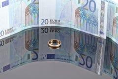 Guld- vigselring på bakgrunden av eurosedlar Arkivfoto