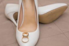 Guld- vigselringar är på skor Royaltyfri Bild