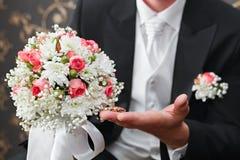 Guld- vigselringar förestående av brudgummen Royaltyfria Bilder