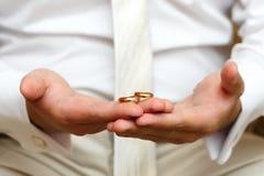Guld- vigselringar förestående av brudgummen Arkivfoton