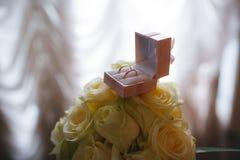 Guld- vigselringar i en ask Arkivfoto