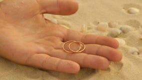 Guld- vigselringar i havssanden arkivfilmer