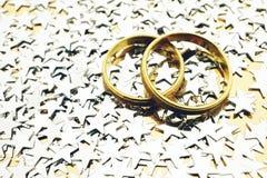 Guld- vigselringar med silverstjärnor royaltyfri foto