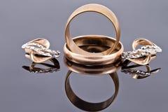 Guld- vigselringar och guld- örhänge Arkivfoto