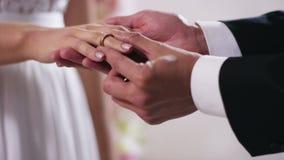 Guld- vigselringar och händer av precis nära övre för gift par förestående av en pålagd man en förlovningsring på fingret arkivfilmer