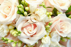 Guld- vigselringar på bukett av blommor för bruden Royaltyfria Bilder