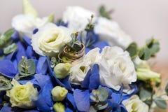 Guld- vigselringar på en bukett av vit- och blåttblommor Royaltyfri Fotografi