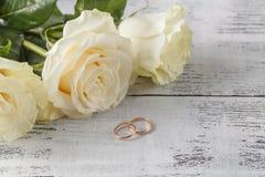 Guld- vigselringar på en bukett av vita rosor Arkivbilder