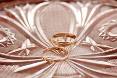 Guld- vigselringar på en platta Royaltyfri Bild
