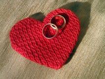 Guld- vigselringar på en röd stucken hjärta Royaltyfri Fotografi