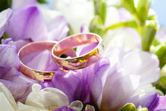 Guld- vigselringar på bukett av blommor för bruden Arkivbilder