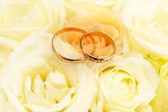 Guld- vigselringar på bukett av blommor för bruden Royaltyfri Bild