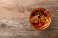 Guld- whisky i exponeringsglas med iskuber på trätabellen, bästa sikt royaltyfri bild