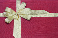 Guldband med bowen på röd kanfastextur Arkivfoto