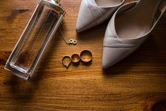 Guldbröllopcirklar, brud- skor och doft på brun bakgrund _ Royaltyfri Foto