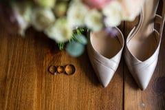 Guldbröllopcirklar, förlovningsringar och brud- skor för en beiga på brun bakgrund _ Arkivbild