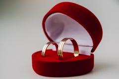 Guldbröllopcirklar i röd ask formen en hjärta Arkivfoto