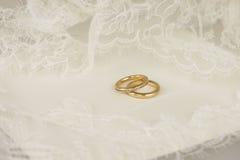 Guldbröllopcirklar med broderat snör åt royaltyfria foton